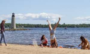 girl doing a cartwheel on the beach as her friends sit on a blanket and smile