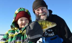 Children holding up caught fish on winter day