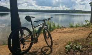 bike next to a post by a lake on a stone trail