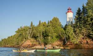 two people in their pwn kayak paddling by a lighthouse