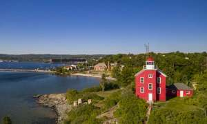 red light house in marquette with lake superior in the background blue sky