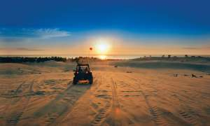 A dune buggy rides into the sunset at Silver Lakes Sand Dunes.