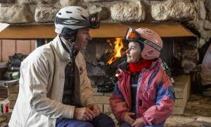 Father and daughter in coats by fire place