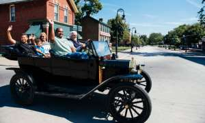 Family in old-fashioned car at Greenfield Village