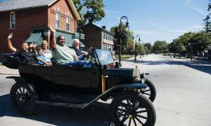 A family trying a Model-T car at Greenfield Village.
