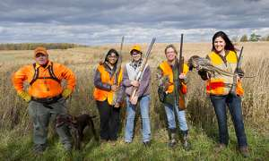 Group of hunters with hunted pheasants
