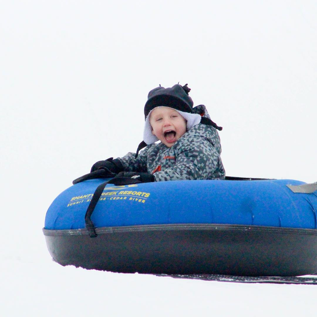 Child laughing in snow tube