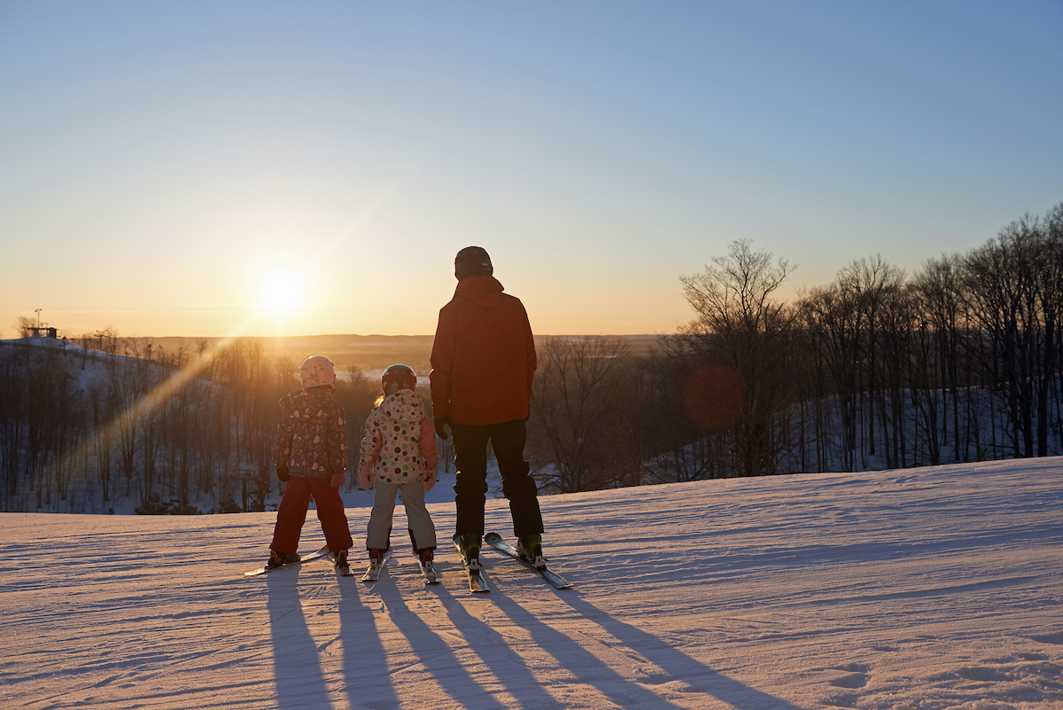 Dad and daughters sunset skiing Crystal Mountain