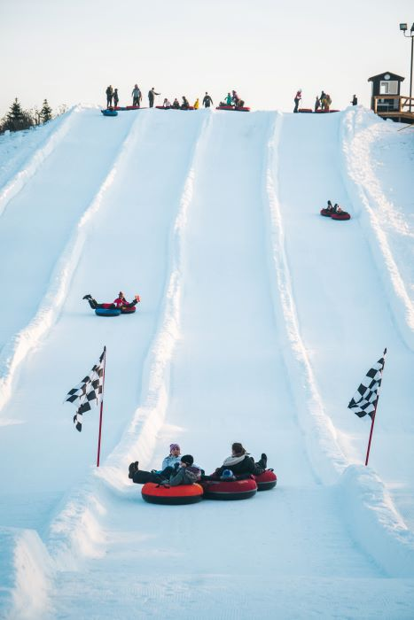 people riding snow tubes on snowy hill