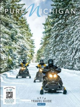 Winter Travel Guide Cover with snowmobilers traveling through winter forest