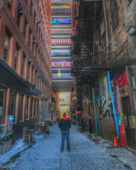 Traveler standing in alley painted with graffiti created by artists