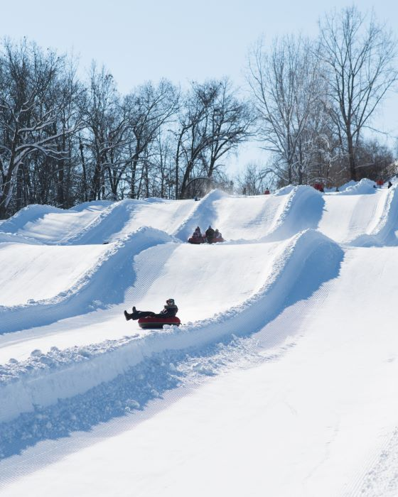People riding snow tubes down snowy hill
