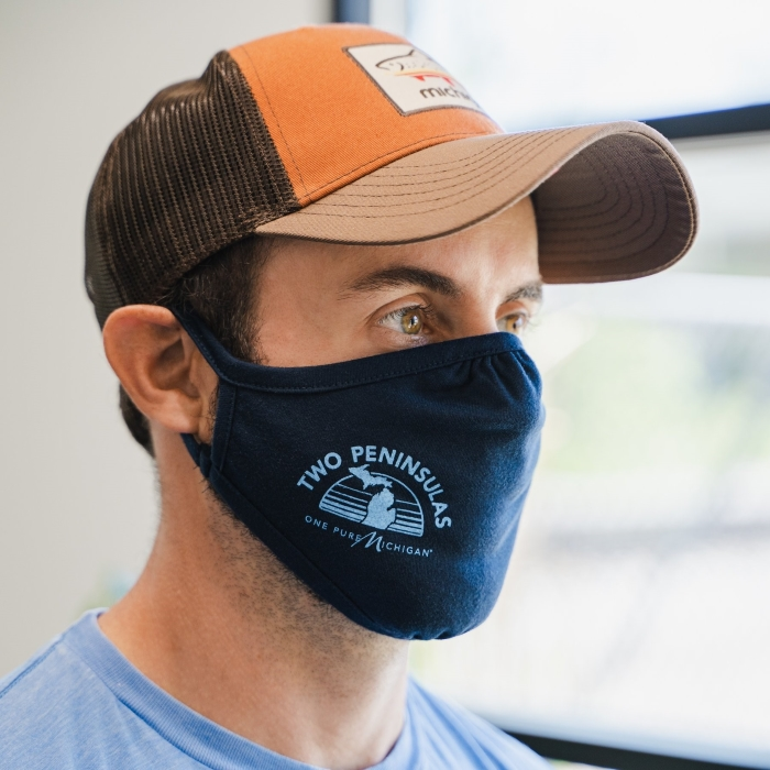 Adult man wearing a cloth facemask with a graphic design