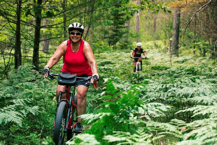 Woman and man mountain biking in forest.