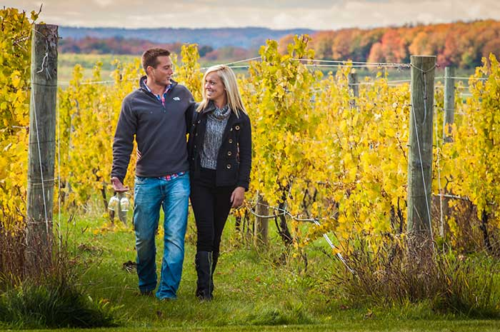 Couple walking through vineyard in Traverse City