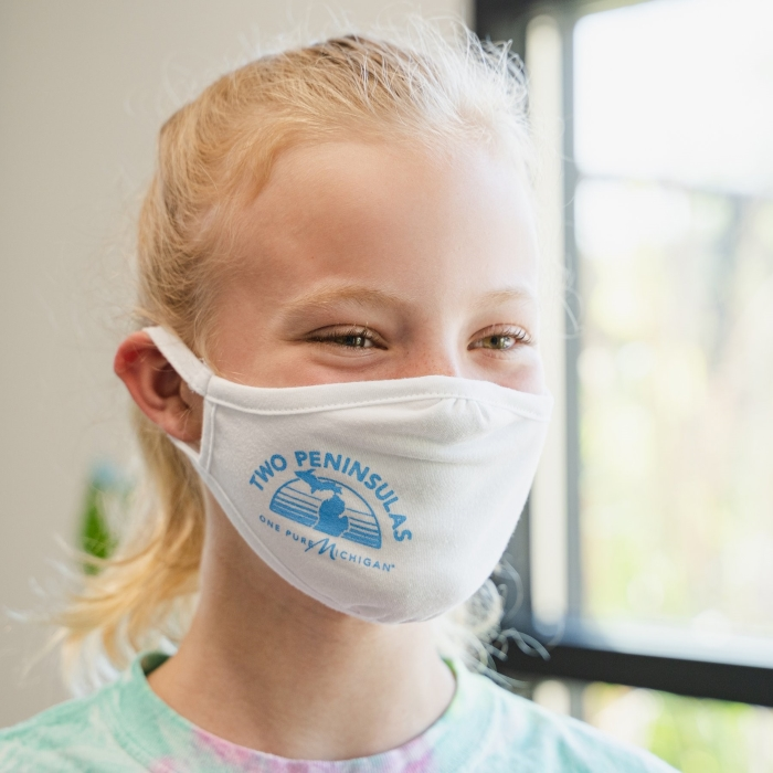 Young girl wearing a cloth facemask with a graphic design