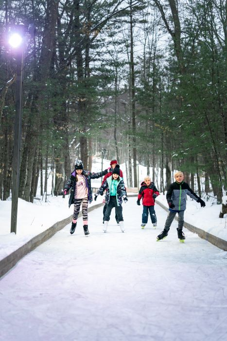 Children ice skating on frozen trail in a forest.