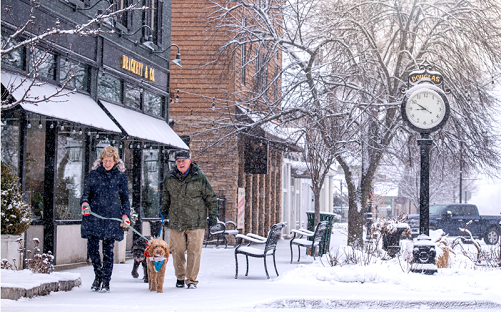 Couple walking with dog in downtown Saugatuck during winter.