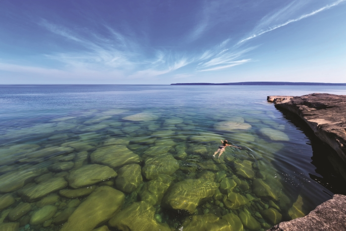Woman swimming in water at Paradise Cove on Lake Superior.