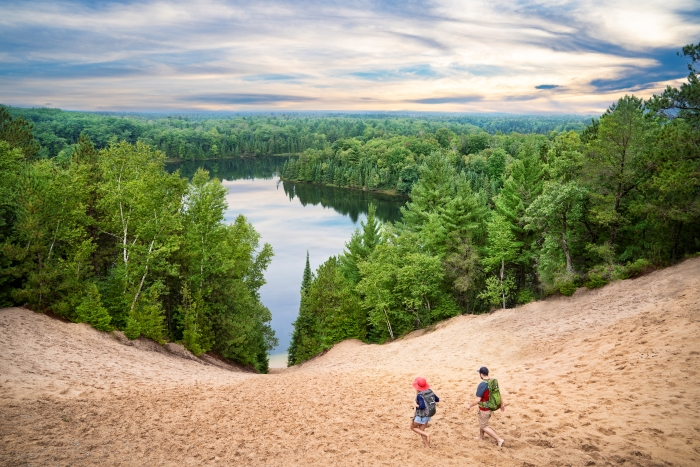 A man and woman walking down the Au Sable River dune surrounded by forest.