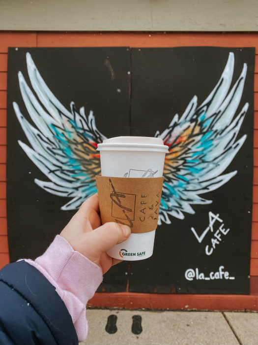 To-go coffee held in front of a mural.